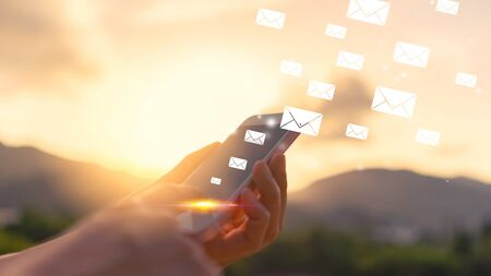 Woman hand using smart phone on top of mountain with email icon flying abstract background. Copy space technology business and travel nature holiday concept. Vintage tone filter effect color.