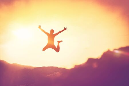Happy man jumping at top of mountain with sunset sky abstract background. Freedom feel good and summer vacation concept. Vintage tone filter effect color style. Archivio Fotografico - 133536427