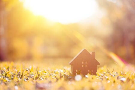 Copy space of home and life concept. Small model home on green grass with sunlight abstract background. Vintage tone filter effect color style.