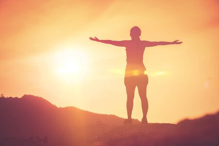 Copie el espacio de la silueta de la mujer levante la mano en la cima de la montaña y el fondo abstracto de la nube del cielo al atardecer. Libertad sentirse bien y viajar concepto de vacaciones de aventura. Estilo de color de efecto de filtro de tono vintage Foto de archivo