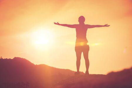 Kopieer de ruimte van silhouet vrouw steek hand omhoog op de top van berg en zonsondergang hemel wolk abstracte achtergrond. Vrijheid voel je goed en reis avontuurlijk vakantieconcept. Vintage toonfilter effect kleurstijl Stockfoto