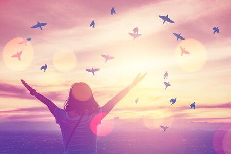 Copiez l'espace de la femme silhouette lève la main au sommet du ciel de la montagne et du coucher du soleil avec des oiseaux volent abstrait. Concept d'aventure de liberté et de voyage. Style de couleur d'effet de filtre de ton vintage.
