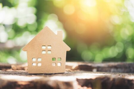 Small home model on wooden table with nature green bokeh abstract background. Family life and business real estate concept. Vintage tone filter effect color style. Archivio Fotografico