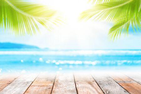 Desenfoque de la playa tropical con la onda de luz del sol del bokeh y la palmera en el espacio de la copia fondo abstracto vacío de la tabla de madera vieja. Presentación del producto en la naturaleza. Estilo de color de efecto de filtro de tono vintage. Foto de archivo