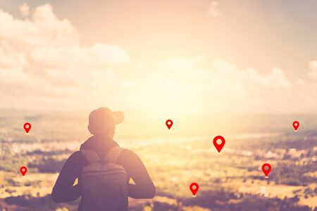Backpacker man standing at top of mountain looking view landscape with navigator gps location abstract background. Copy space travel adventure holiday and technology business concept. Vintage color 免版税图像