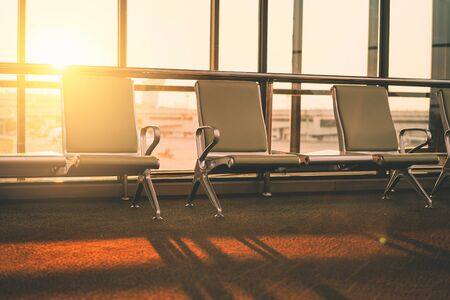 Empty chair in airport terminal gate with window sunset light background. Travel adventure and vacation freedom concept. Vintage tone filter effect color style.