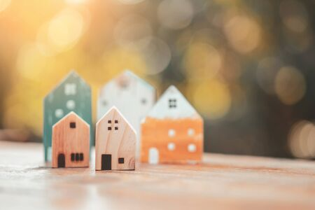 Small home model on wooden table with nature green bokeh abstract background. Family life and business real estate concept. Vintage tone filter effect color style. Banco de Imagens