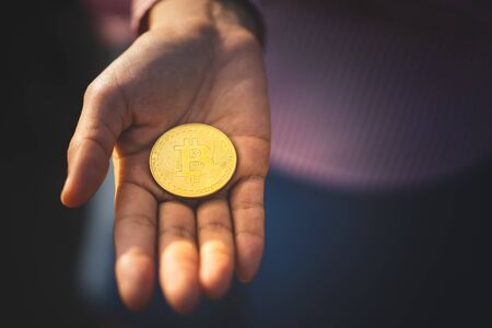 Bitcoin on woman hand background. Technology business and financial concept. Vintage tone filter effect color style