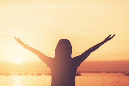 Copia lo spazio della donna alza la mano sul cielo al tramonto in spiaggia e sullo sfondo dell'isola. Libertà e concetto di avventura di viaggio. Stile di colore effetto filtro tono vintage.