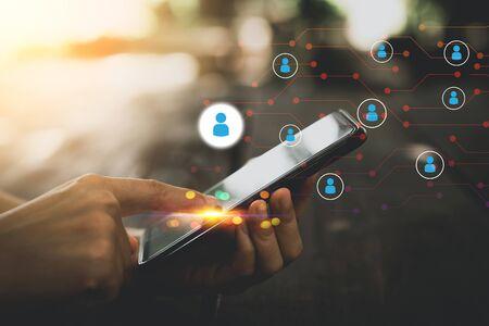 Kobieta ręka za pomocą inteligentnego telefonu w kawiarni z ludźmi ikona i linia kropka streszczenie tło. Technologia biznesowa i koncepcja komunikacji połączenia. Styl koloru efektu filtra tonalnego w stylu vintage.
