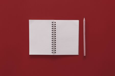 Notebook and pencil on red texture background.