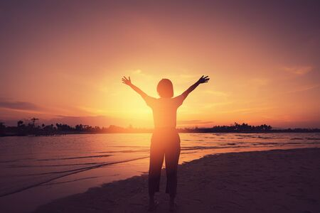 Copy space of woman rise hand up on sunset sky at beach and island background. Freedom and travel adventure concept. Vintage tone filter effect color style. Stockfoto