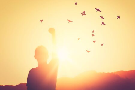 Freedom feel good and travel adventure concept. Copy space of silhouette man rising hands on sunset sky at top of mountain and bird fly abstract background. Vintage tone filter effect color style.