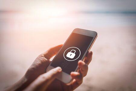 Frauenhand, die Smartphone am Sonnenuntergangstrand mit Schlossikonenhintergrund verwendet Technologiegeschäft und Reisefreiheitskonzept. Farbstil mit Vintage-Tonfiltereffekt.