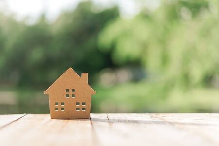 Small home model on wooden table with nature green bokeh abstract background. Family life and business real estate concept. Vintage tone filter effect color style. Imagens