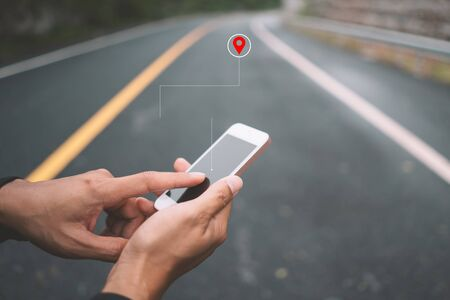 Man hand using smartphone with gps navigator map icon on blur street background. Technology lifestyle and business travel concept. Vintage filter effect color style. Standard-Bild