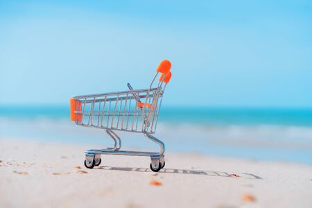 Shopping basket cart on sand beach with blue sky background. Summer sale and business service concept. Vintage tone filter effect color style. Standard-Bild