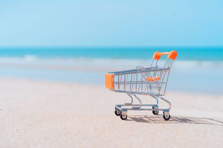 Shopping basket cart on sand beach with blue sky background. Summer sale and business service concept. Vintage tone filter effect color style. Stok Fotoğraf