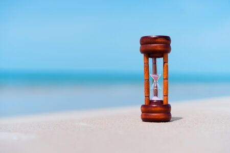 Hourglass on sand beach with blue sky background. Vintage tone filter effect color style.