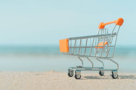 Shopping basket cart on sand beach with blue sky background. Summer sale and business service concept. Vintage tone filter effect color style. 免版税图像