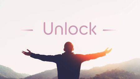 Unlock words with man raise hand up on top of mountain and sunset sky abstract background. Freedom and travel adventure concept. Vintage tone filter effect color style.