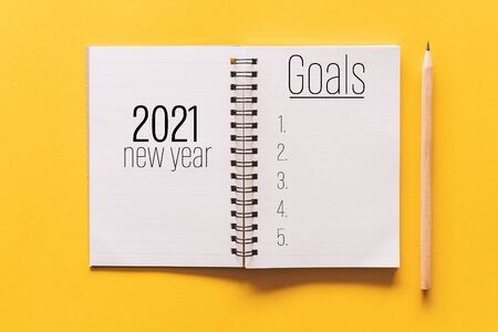 2021 new year goals on notebook with pencil. Pastel color background.