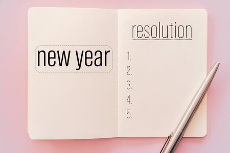 New year resolution on notebook with pen. Pastel color background. 免版税图像