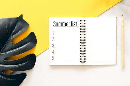 Notebook pencil and green leaf with summer list words on yellow background.