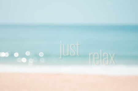 Just relax words on blur tropical beach with bokeh sunlight wave abstract background. Summer vacation and travel holiday concept. Vintage tone filter effect color style.