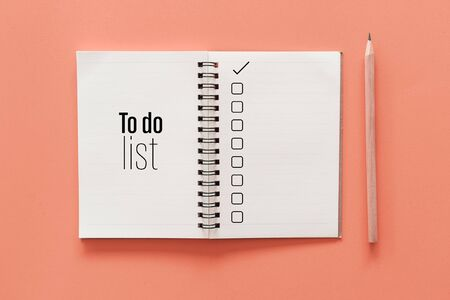 Notebook and pencil with to do list words on pastel color background. 免版税图像