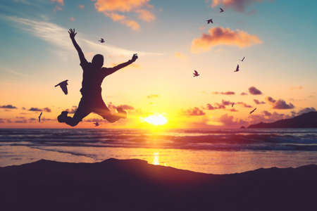 Happy man jumping at tropical beach with birds flying on sunset sky abstract background. Freedom feel good and travel adventure concept. Vintage tone filter effect color style.