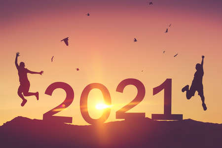 Silhouette friends jumping and birds flying on sunset sky at top of mountain and number like 2021 abstract background. Happy new year and holiday celebration concept. Vintage tone filter color style.
