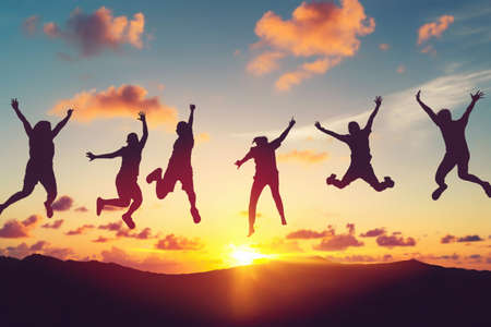 Silhouette happy friends jump at top of mountain on sunset sky abstract background. Copy space of feel good freedom and travel adventure concept. Vintage tone filter effect color style. Zdjęcie Seryjne