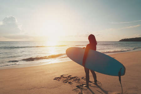 Woman hold surfboard standing at tropical sunset beach background. Summer vacation and sport adventrue concept. Vintage tone filter effect color style.