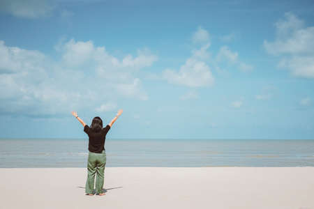 Happy woman raises hand up at the tropical beach with blue sky Banco de Imagens