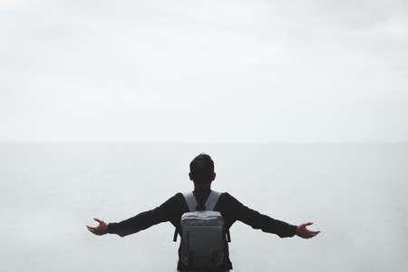 A man raises his hand upon blue sky at the beach Banco de Imagens - 164033587