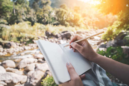 Woman hand writing on notebook with pencil at river background. Banco de Imagens - 164062040
