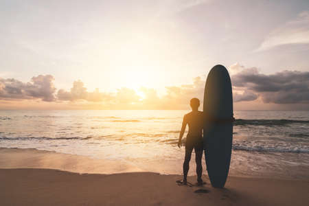 Man hold surfboard standing at tropical sunset beach background. Summer vacation and sport adventrue concept. Vintage tone filter effect color style. Banco de Imagens - 163640169