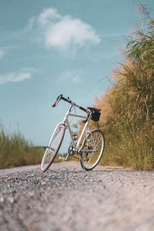 Vintage bicycle on country road and field with blue sky and white cloud abstract background. Banco de Imagens - 163640151