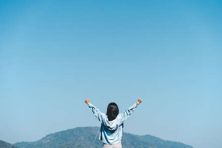Copy space of woman raise hand up on top of mountain and blue sky cloud abstract background. Freedom feel good and travel adventure holiday concept. Vintage tone filter effect color style