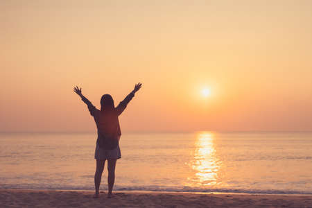 Copy space of woman rise hand up on sunset sky at beach and island background. Freedom and travel adventure concept. Vintage tone filter effect color style. Foto de archivo