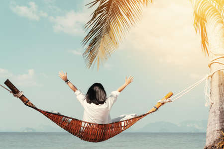 Happy woman hand raising and sitting on hammock at tropical beach background. Summer vacation and freedom feel good concept. Vintage tone color style.