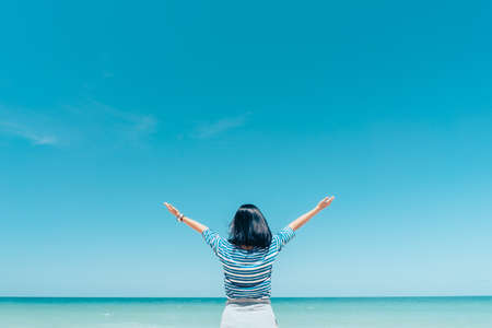 Happy woman raises her hand up at a tropical beach with blue sky