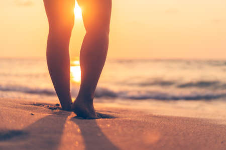 Close up woman legs walking on tropical sunset beach with smooth wave and bokeh sun light wave abstract background. Travel vacation and freedom feel good concept. Vintage tone filter color style. Banco de Imagens