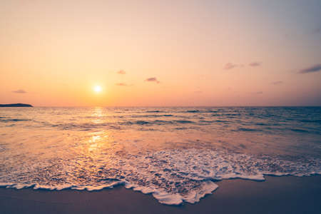 Tropical beach with smooth wave and sunset sky abstract background. Copy space of business summer vacation and travel adventure concept. Vintage tone filter effect color style.