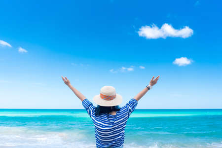 Happy woman raise hand up at tropical beach with blue sky background. Travel vacation and freedom feel good concept. Vintage tone filter effect color style. Banco de Imagens