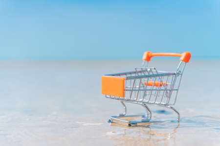Shopping basket cart on sand beach with blue sky background. Summer sale and business service concept. Vintage tone filter effect color style. Banco de Imagens