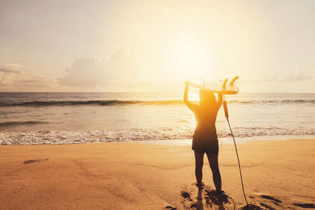 Woman hold surfboard standing at tropical sunset beach background. Summer vacation and sport adventrue concept. Vintage tone filter effect color style. Stock fotó