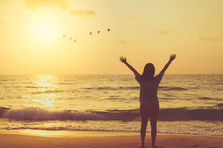 Copy space of woman raise hand up on sunset sky at beach and island with birds flying abstract background. Freedom and travel adventure concept. Vintage tone filter color style.