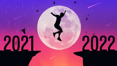 Silhouette man jumping and birds flying between cliff with number 2021 to 2022 at top of mountain on full moon sunset sky background. Freedom challenge and travel adventure holiday concept. Stock Photo